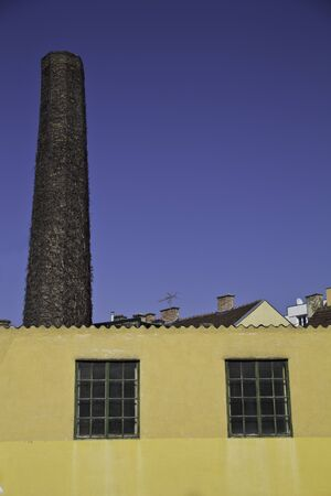 An old factory with a chimney in urban setting Stock Photo