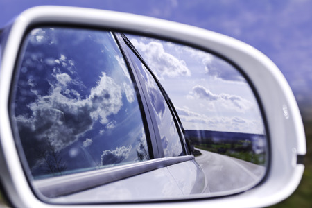 An impressive cloudscape reflected in the mirror and car while driving on a beautiful day