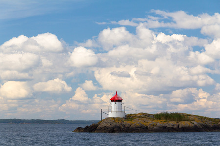 navigation aid: A lighthouse in the baltic on a typical scnadinavian half sunny day. Stock Photo