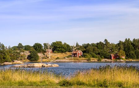 The typical red houses beyond a bay in the baltic sea in best summer weather