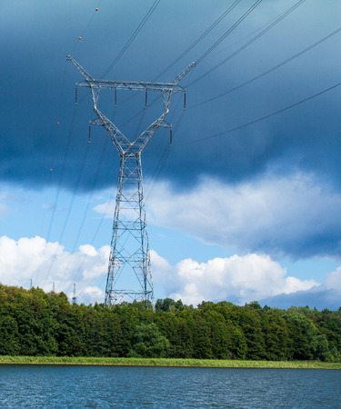 over voltage: A high voltage power line stretching over land and water while a storm is brewing.