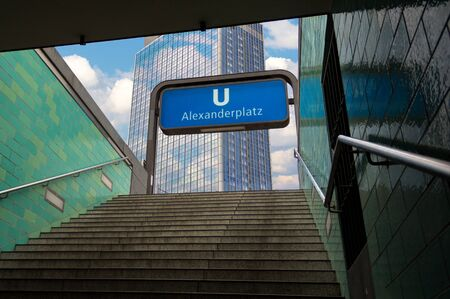 The subway sign of Berlin Alexanderplatz with a view of the new buikdings above ground.