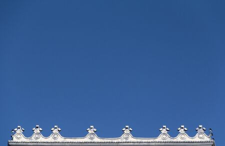 A decorative finish of a roof against a very blue sky. Stock Photo