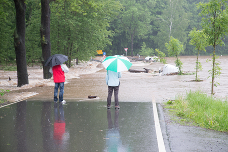 Climate change? Flood 2013 - 2 passersby stand on the flooded road in rain and flood