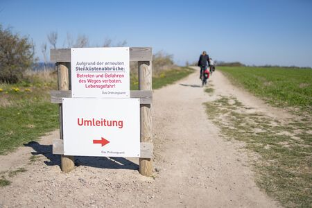 Ignore the warning signs for the steep cliffs at the Baltic Sea at the Baltic Sea resort of Ahrenshoop Translation