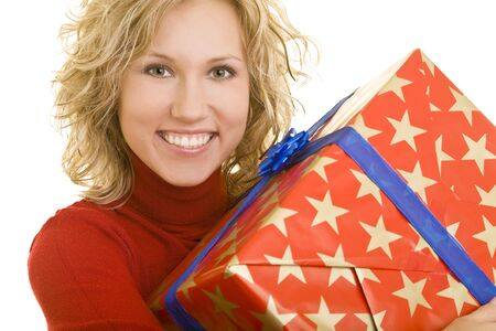 Young smiling woman in a red pullover carrying a wrapped gift photo