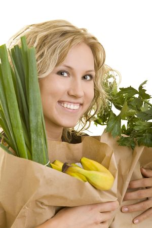 Smiling woman carries fruits and vegetables in brown paper bags photo