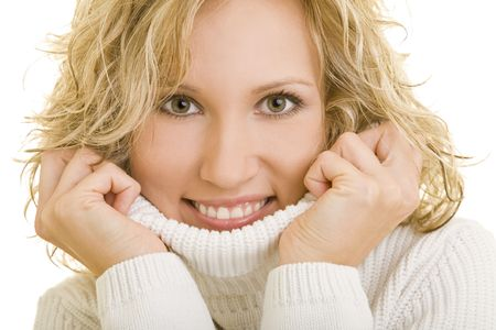Young blond woman holding the turtleneck of her white sweater photo