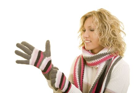 getting late: Young woman puts on gloves on her hands Stock Photo