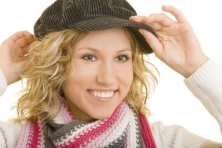 flat cap: Smiling blond woman putting a flat cap on her head Stock Photo