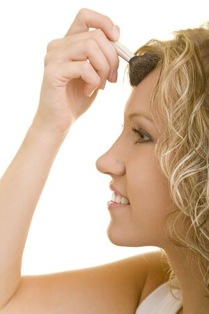 20 25: Blonde woman applies face powder on her forehead Stock Photo