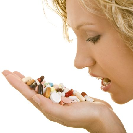 Blonde woman holding a heap of pills in her palm photo