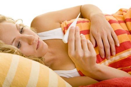 Blonde woman in bed looking at a clinical thermometer photo