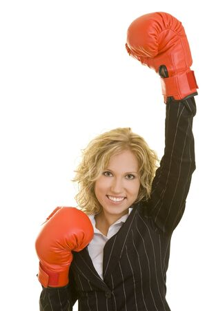 Blonde business woman holding up her red boxing gloves photo