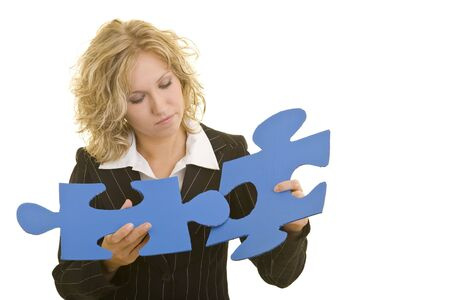 Blonde business woman putting together two blue jigsaw pieces photo