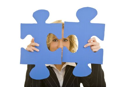 Blonde business woman looking through two jigsaw pieces photo