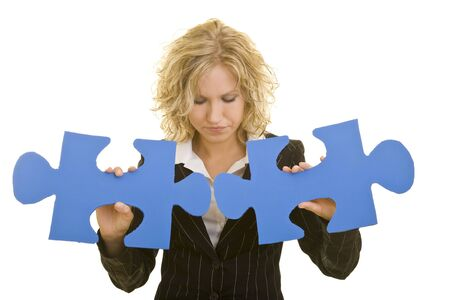 Blonde business woman trying to connect two oversized blue jigsaw pieces photo