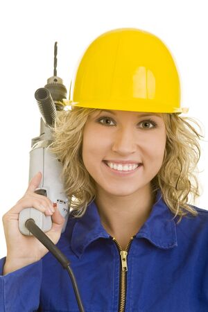 Young woman with helmet and jumpsuit carrying a drill machine on her shoulder photo