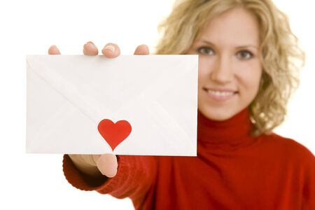 Blonde woman holding a white letter with a red heart shaped sticker on it photo
