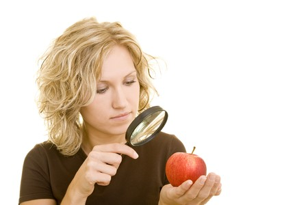Blonde woman is looking at an apple with a magnifying glass photo