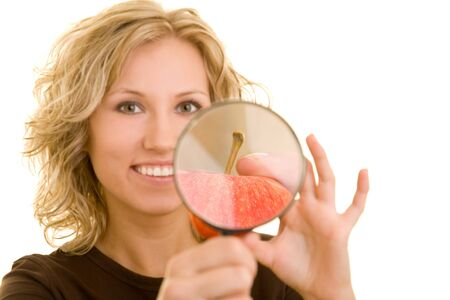 scrutiny: Blonde Woman holding an apple and a magnifying glass