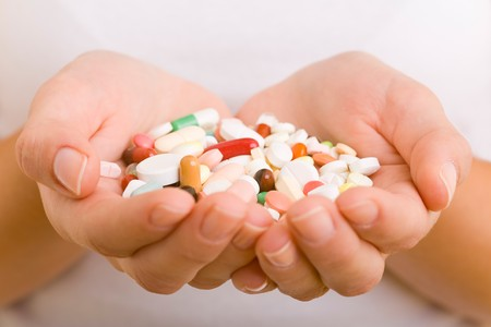 Hands holding a variety of pills and capsules photo