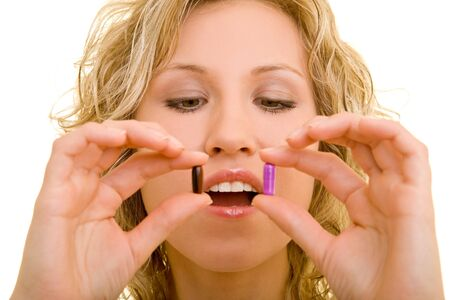 Blonde woman holding two pills in her hands photo