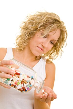 Blonde woman holding a glass with many pills photo