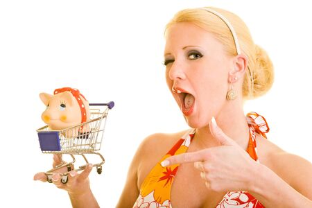 Blonde woman holding a small shopping cart with a piggy bank inside photo