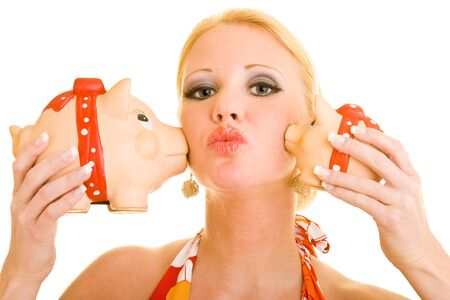 blond woman gets kisses from two piggy banks on her cheeks photo