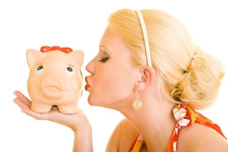 Blonde woman kissing a piggy bank photo