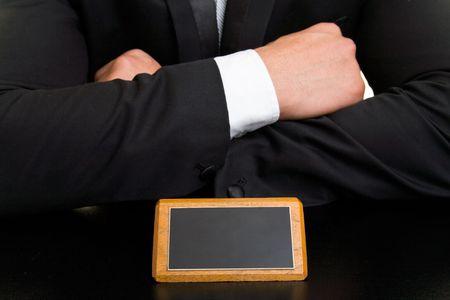 mensch: Manager mit verschr�nkten Armen vor einem leeren Schild auf dem Schreibtisch Stock Photo