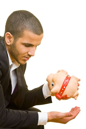 Young business man holding his hand under an empty piggy bank photo