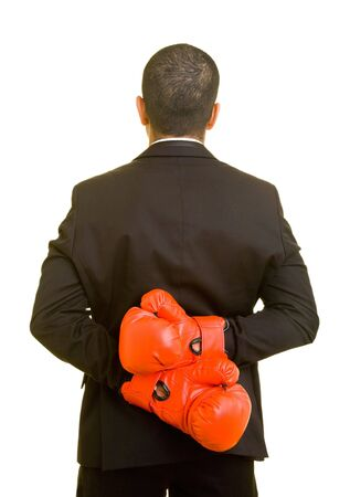 clandestine: Business man hiding boxing gloves behind his back Stock Photo