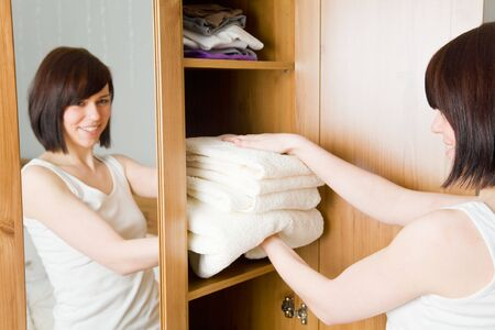 Young woman with white towels in her wardrobe
