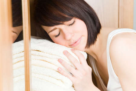 Young woman with white towels in her wardrobe photo