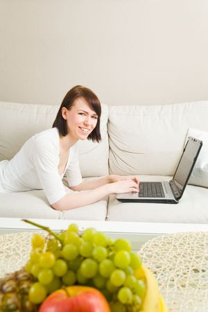contentedness: Young woman working on a laptop on a sofa