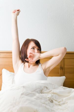 sleepiness: Young woman waking up in her bed
