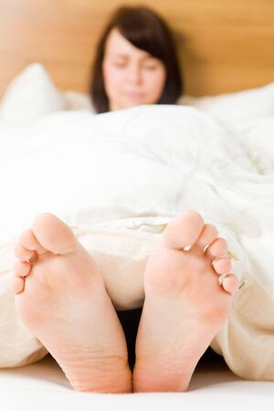 black toes: Young woman in her bed with feet outside the blanket Stock Photo
