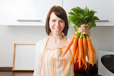 Young woman in her kitchen holding a bundle of carrots photo