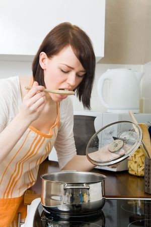 boiling: Young woman cooking in her kitchen Stock Photo