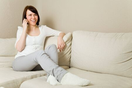 Happy young woman on her mobile phone in the living room Stock Photo - 4824247