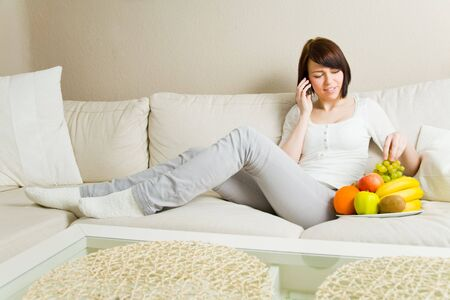 Happy young woman on her mobile phone in the living room eating fruits photo