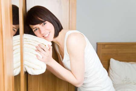 Laundry: Mujer joven con toallas blancas en su armario