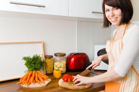 cuchillo de cocina: Mujer joven en su cocina ingredientes de corte Foto de archivo
