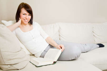 Young woman reading a book in her living room photo