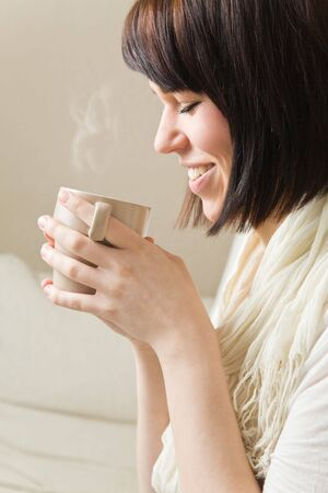 sense: Young woman drinking a hot cup of coffee