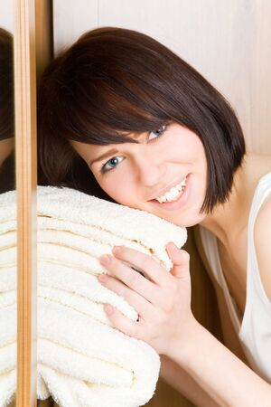 tidiness: Young woman with white towels in her wardrobe