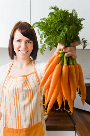 Young woman in her kitchen holding a bundle of carrots Stock Photo - 4860276