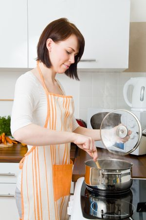 stirring: Young woman cooking in her kitchen Stock Photo